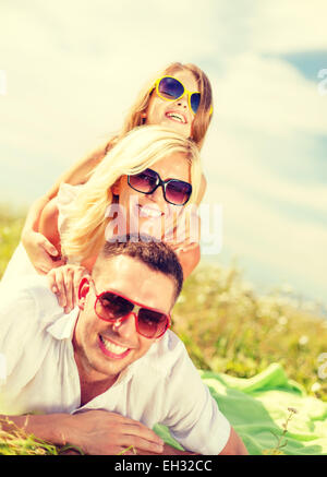 Smiling family in sunglasses lying on blanket Banque D'Images