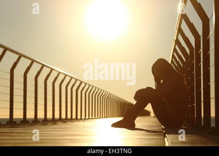 Triste fille adolescent déprimé assis sur le plancher d'un pont sur la plage au coucher du soleil Banque D'Images