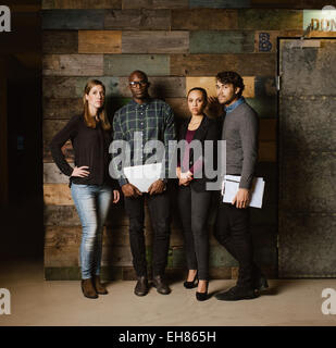 Longueur totale de l'image de l'équipe des Créatifs multiraciale qui pose pour appareil photo de bureau. Les jeunes gens d'affaires se tenant ensemble contre un wo