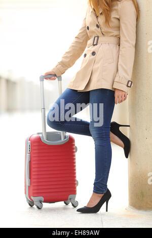 Vue verticale d'un touristiques femme jambes en attente avec une valise dans un aéroport ou gare