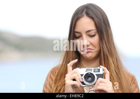 Femme photographe bouleversé à son ancien appareil photo reflex dégoûté de la mer en arrière-plan Banque D'Images