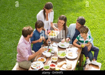 Famille et amis se rassemblent pour pique-nique Banque D'Images