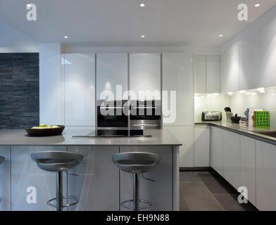 Lit moderne cuisine avec bar et tabourets et mur de pierre fonctionnalité dans Walham Grove accueil, UK Banque D'Images