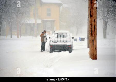 Un homme les éraflures de la neige de sa voiture à London, Ontario au Canada. Banque D'Images