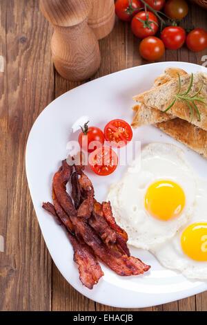 Oeufs au plat et du bacon sur une plaque avec des épices et des légumes. Studio shot Banque D'Images