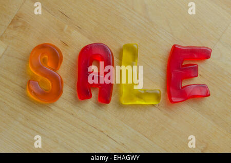 Bonbons colorés lettres épeler le mot vente Banque D'Images