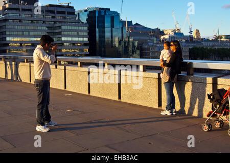 Un homme de prendre une photo de sa femme et son enfant sur le pont de Londres au coucher du soleil Banque D'Images