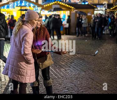 Deux jeunes filles de prendre une photo à selfies Marché de Noël, Strasbourg, Alsace, France Banque D'Images