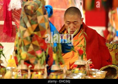 DREPUNG, Tibet, Chine-OCTOBRE 19: moine bouddhiste tibétain lit les textes sacrés dans le Sutra Hall de la salle Banque D'Images