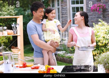Père tenant sa fille à l'alimentation des tomates mère Banque D'Images