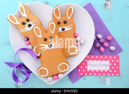 Lapin de Pâques gingerbread cookies sur la plaque en forme de coeur avec carte de vœux. Banque D'Images