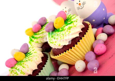 Happy Easter Bunny cupcakes avec les oeufs de Pâques sur la table en bois de rose. Banque D'Images