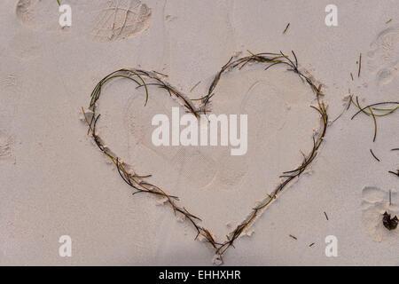 Cœur percé par la flèche de Cupidon dessiné dans le sable Banque D'Images