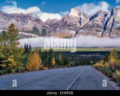 La route, le brouillard et les nuages bas aux couleurs de l'automne. Le parc national Banff. L'Alberta, Canada Banque D'Images