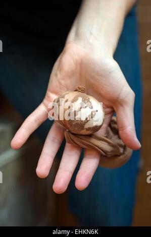 Un oeuf enveloppé en collants avec oignon skins et lin, prêt à être en durs colorant décoratifs pour Pâques. Banque D'Images