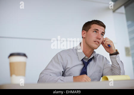 Caucasian businessman sitting in office Banque D'Images