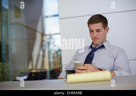 Caucasian businessman using cell phone in office Banque D'Images