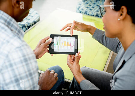 Black business people using digital tablet in office lobby Banque D'Images