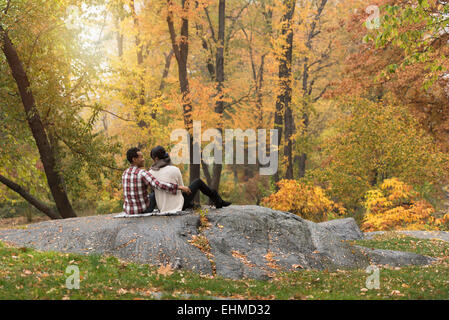 Asian couple hugging on rock in park Banque D'Images
