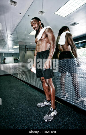 African American man standing at mirror in gym Banque D'Images