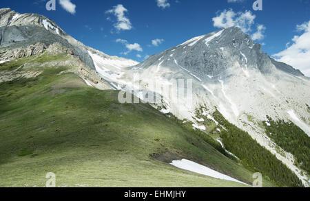 Des pics de montagne avec de la neige et de l'herbe sous ciel bleu Banque D'Images