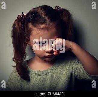 Malheureux enfant fille pleurer dans l'obscurité. Closeup portrait vintage Banque D'Images