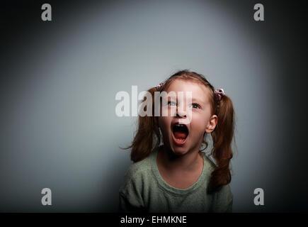 Fille enfant en colère crier avec bouche ouverte et à la recherche jusqu'au mal sur fond sombre Banque D'Images