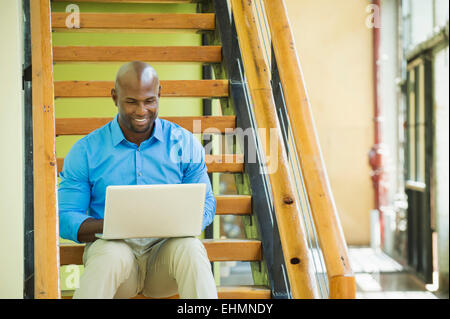 Black businessman using laptop on staircase Banque D'Images