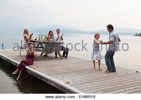 Caucasian family cheering comme père et fille danser sur la jetée sur le lac Banque D'Images