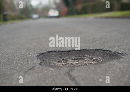 Besoin de réparer un nid-de-poule se trouve au milieu d'une route tarmacked créant un trou pour jeter les cyclistes Banque D'Images