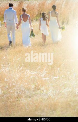 Jeune couple avec et de demoiselle girl walking in meadow Banque D'Images
