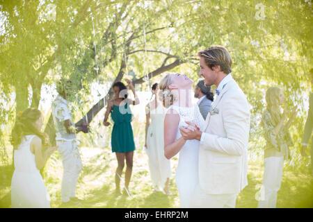 Young couple dancing at wedding reception dans le jardin intérieur Banque D'Images