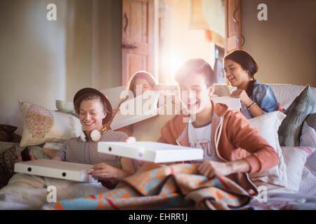 Groupe d'adolescents l'ouverture de boîtes à pizza on sofa in living room Banque D'Images