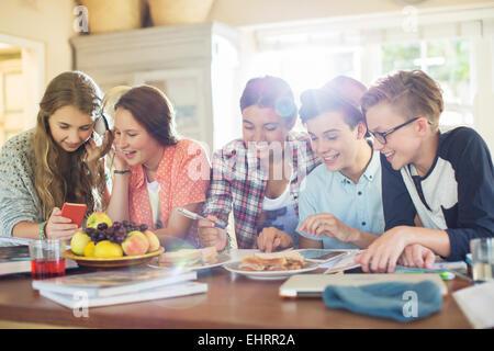 Groupe d'adolescents à l'aide de dispositifs électroniques à table dans la salle à manger Banque D'Images