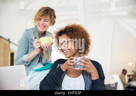 Deux employés de bureau talking at desk using laptop Banque D'Images