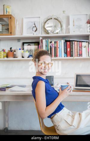 Jeune femme assise avec mug in home office