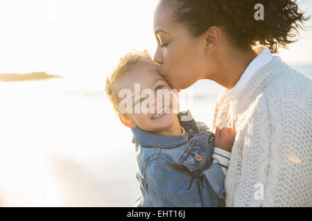 Mother kissing daughter on beach Banque D'Images