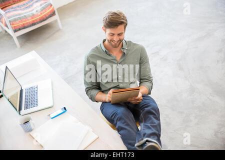 Portrait de jeune homme assis avec les jambes sur le bureau en studio Banque D'Images
