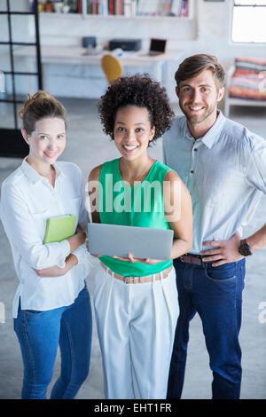 Portrait de trois jeunes gens debout with digital tablet in studio Banque D'Images