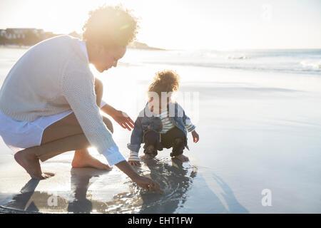 Mère et fille dessin sur sable humide on beach Banque D'Images