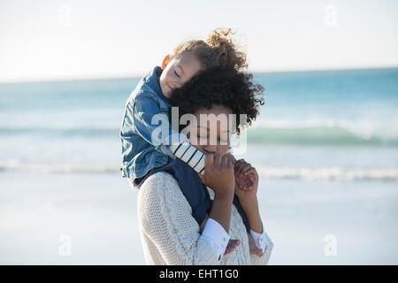 Fille mère portant sur ses épaules on beach Banque D'Images