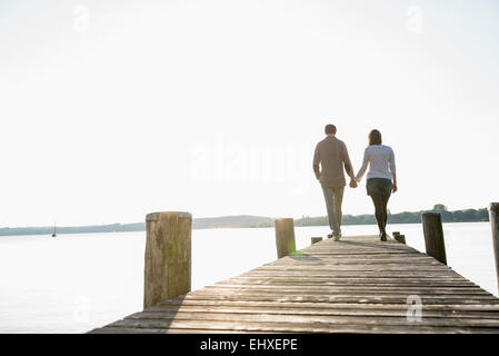 Couple en train de marcher sur la jetée en bois coucher du soleil Banque D'Images
