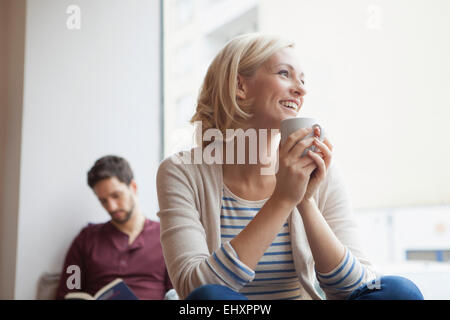 Portrait of happy woman relaxing with cup of tea Banque D'Images