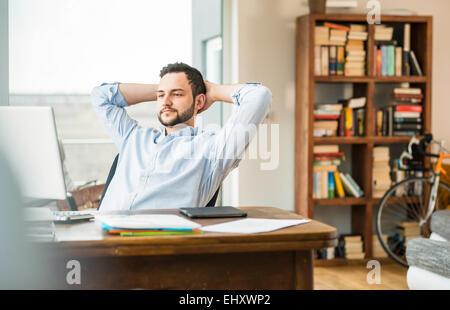 Jeune homme au bureau en se penchant en arrière Banque D'Images