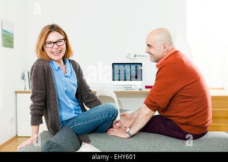 Couple à la maison, l'ordinateur en arrière-plan Banque D'Images
