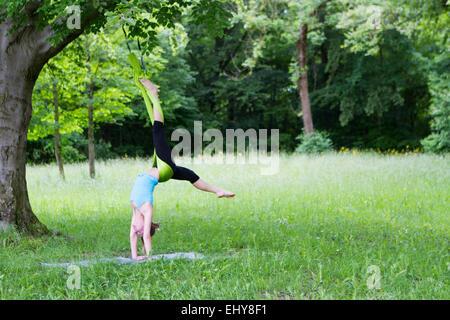 Jeune femme ne s'étendant des exercices avec élastique, Munich, Bavière, Allemagne Banque D'Images