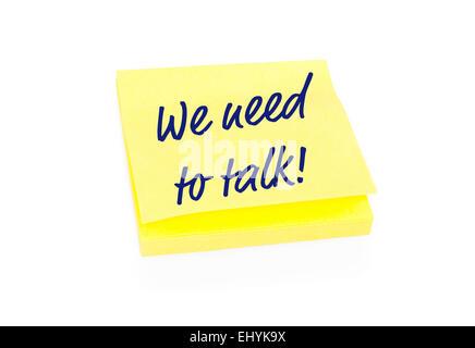 Yellow sticky note sur le bloc avec du texte nous avons besoin de parler Banque D'Images