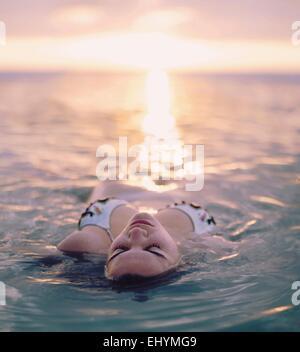 Jeune femme flottant dans la mer, Sanibel Island, Floride, USA Banque D'Images