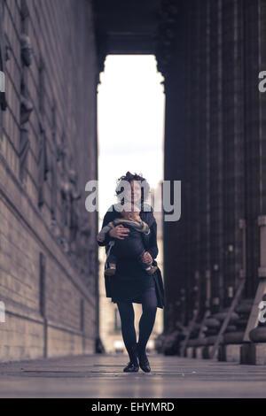 Mid adult woman carrying son fils, Paris, France Banque D'Images