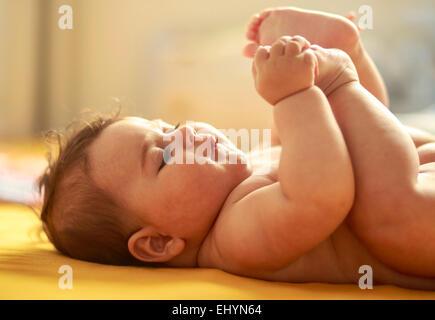 Bébé Garçon jouant avec pieds Banque D'Images